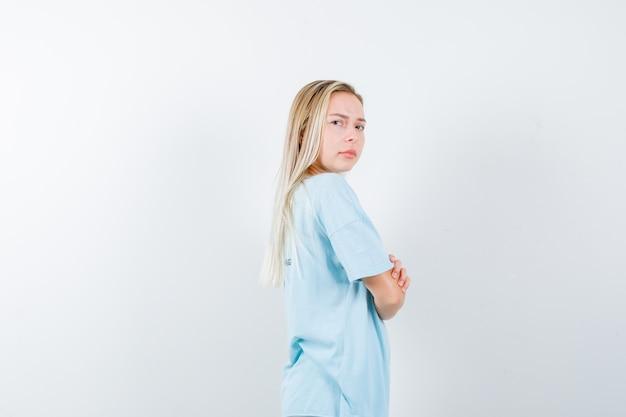 Tシャツで肩越しに見て、自信を持って、正面図を見て、腕を組んで立っている若い女性。