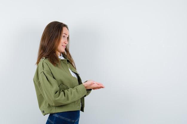 Молодая дама стоит с сложенными чашечками руками в блузке, куртке и выглядит деликатно.