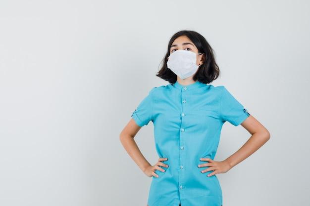 青いシャツ、マスク、自信を持って腰に手を置いて立っている若い女性