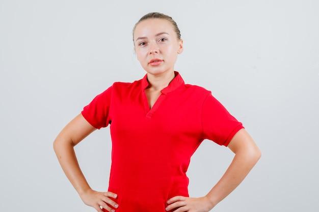 Giovane donna in piedi con le mani sulla vita in maglietta rossa e guardando fiducioso
