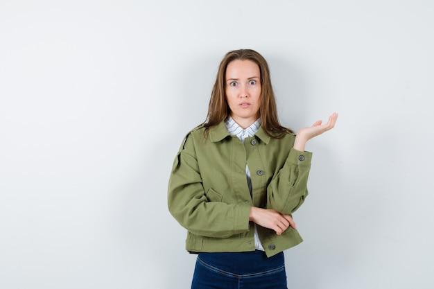 ブラウス、ジャケットに広げられた手のひらで立って、困惑しているように見える若い女性。