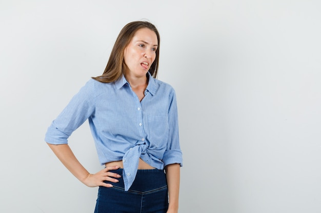 Young lady sticking out tongue in blue shirt, pants and looking disgusted.