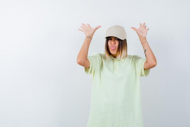 티셔츠, 모자에 항복 제스처에 손바닥을 보여주는 동안 혀를 튀어 나와 무력한 젊은 아가씨. 전면보기.