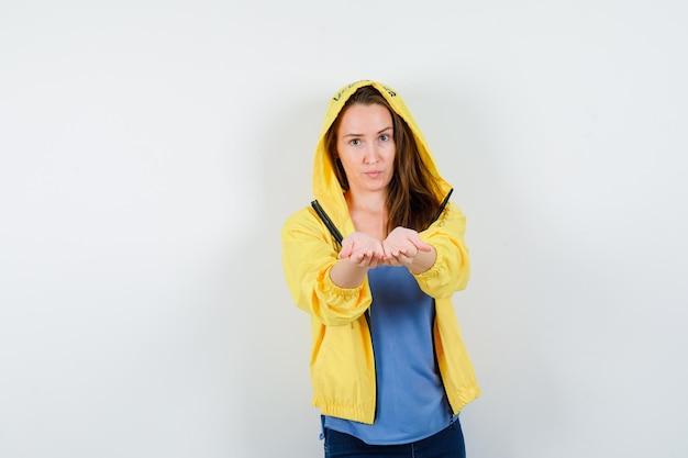 Tシャツ、ジャケットでカップ状の手を伸ばして繊細に見える若い女性