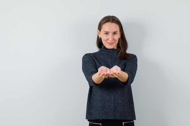 Young lady stretching cupped hands in shirt and looking jolly