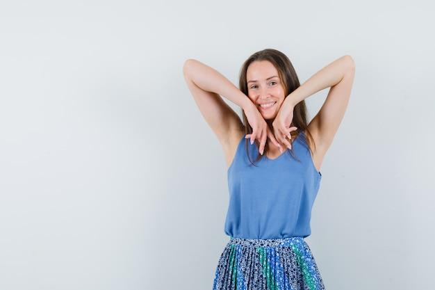 一重項、スカートで肘を伸ばし、楽観的に見える若い女性、正面図。