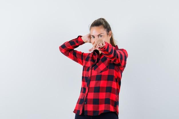 Молодая леди протягивает руку в клетчатой рубашке и выглядит элегантно