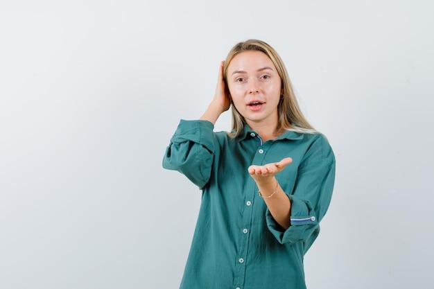 緑のシャツを着て手を伸ばして魅力的に見える若い女性。
