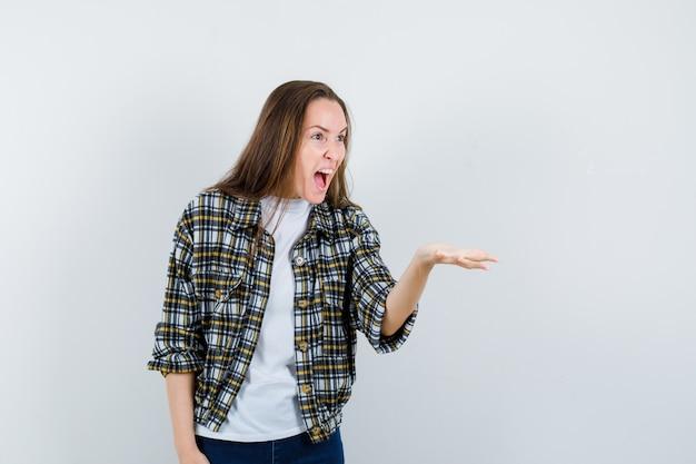 Молодая леди протягивает руку в вопросительном жесте в футболке, куртке, джинсах и выглядит сердитой, вид спереди.