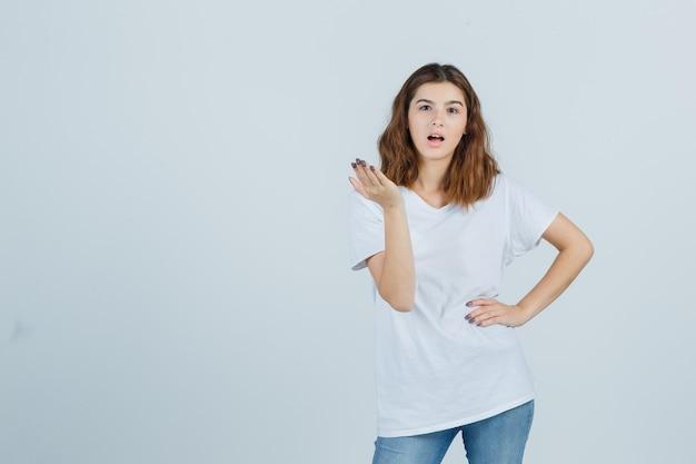 Молодая леди протягивает руку в вопросительном жесте в футболке, джинсах и выглядит озадаченным, вид спереди.