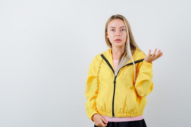 Giovane donna che allunga la mano nel gesto interrogativo in maglietta, giacca e sembra sicura