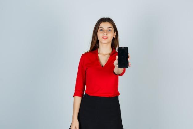 Giovane donna che allunga la mano per mostrare il cellulare in camicetta rossa, gonna e sembra sicura