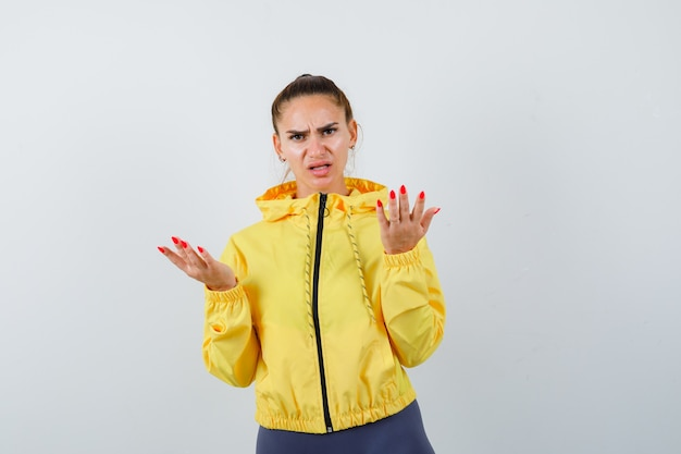 Young lady stretching hands in questioning gesture in yellow jacket and looking serious , front view.