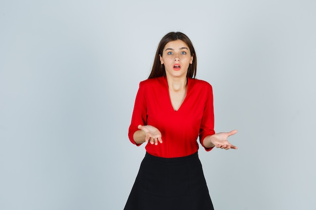 Young lady stretching hands in questioning manner in red blouse