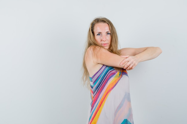 Young lady stretching her arm in summer dress and looking confident