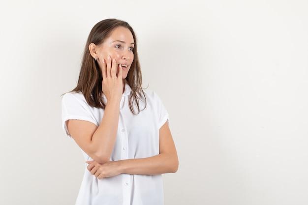 Молодая леди протягивает руки в белой блузке и выглядит счастливой.