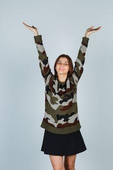 セーター、スカートで上半身を伸ばして陽気に見える若い女性