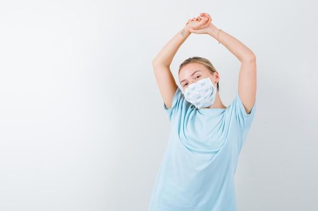 Tシャツ、マスクで上半身を伸ばし、リラックスして見える若い女性