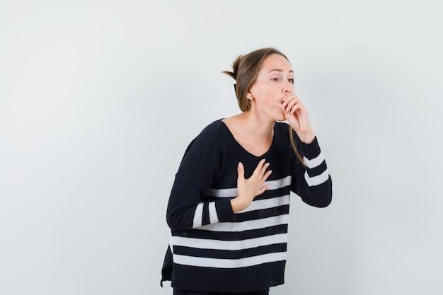 Giovane donna che soffre di tosse in camicia casual e sembra malata