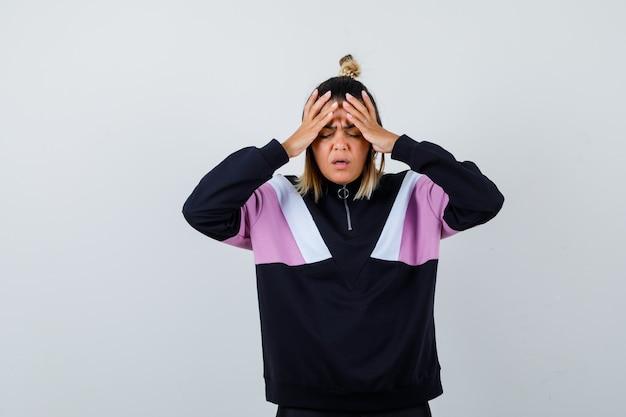パーカーのセーターの頭痛に苦しんでいると痛みを伴う若い女性