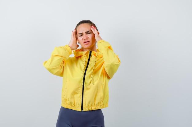 黄色いジャケットの頭痛に苦しんでいて、痛みを伴うように見える若い女性。正面図。