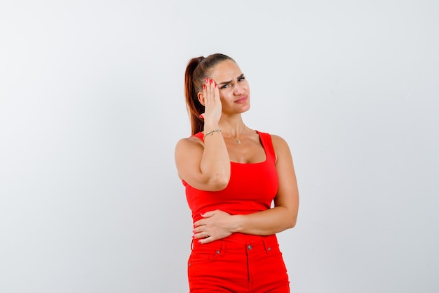 Young lady suffering from headache in red singlet, red trousers and looking painful , front view.