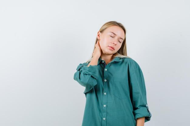 緑のシャツの首の痛みに苦しんでいて、疲れているように見える若い女性。
