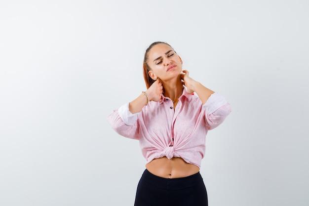 Молодая женщина страдает от боли в шее в рубашке, штанах и выглядит усталой