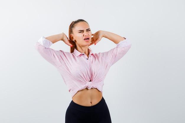 Молодая женщина страдает от боли в шее в рубашке, штанах и выглядит усталой, вид спереди.