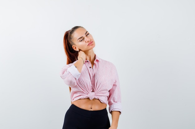 Young lady suffering from neck pain in shirt and looking tired , front view.