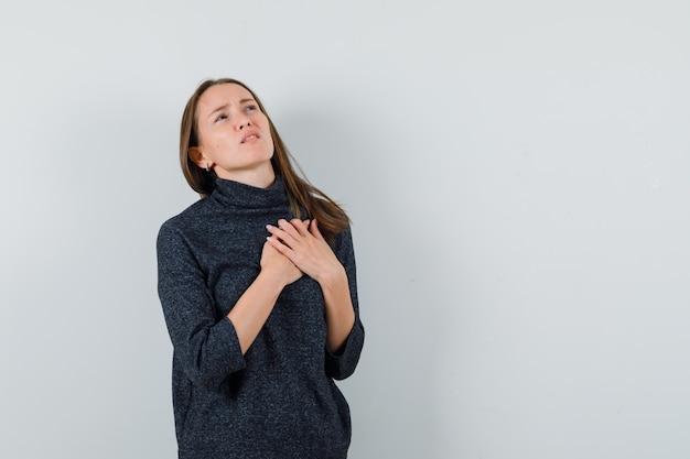 Giovane donna che soffre di dolore al cuore in camicia e non sembra stare bene