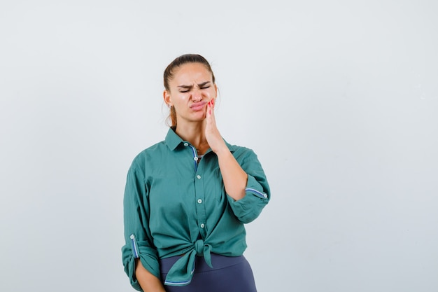 Young lady suffering from painful toothache in green shirt and looking annoyed. front view.
