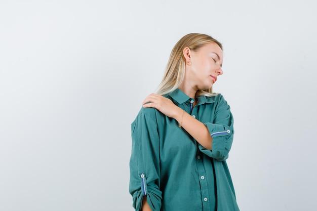 緑のシャツの肩の痛みに苦しんでいて、疲れているように見える若い女性。