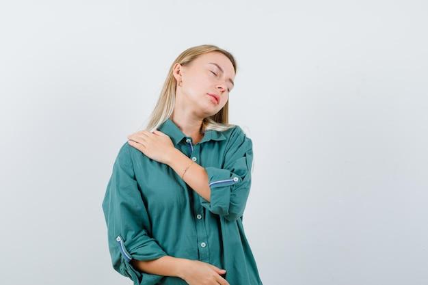 緑のシャツの肩の痛みに苦しんでいて、不快に見える若い女性。