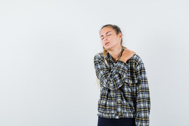 Молодая леди страдает от боли в плече в рубашке, шортах и выглядит усталой, вид спереди.
