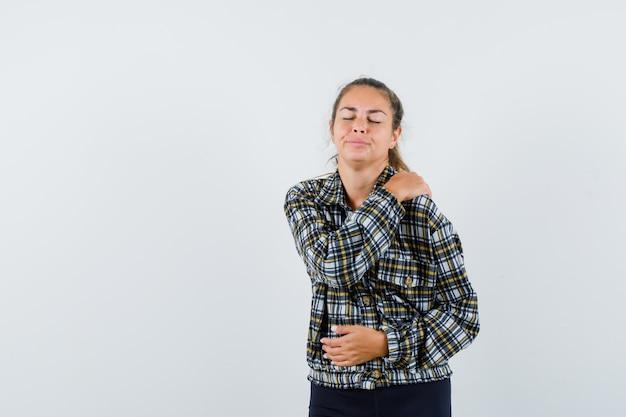셔츠, 반바지에 어깨 통증으로 고통 받고 피곤, 전면보기 젊은 아가씨.