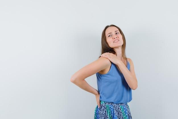 Девушка страдает от боли в плече в майке, юбке и выглядит утомленной. передний план.