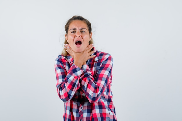Young lady suffering from sore throat in checked shirt and looking sick , front view.
