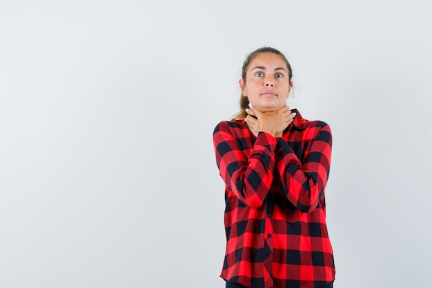 Young lady suffering from sore throat in checked shirt and looking sick