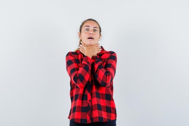 チェックシャツの喉の痛みに苦しんでいる若い女性と病気に見える