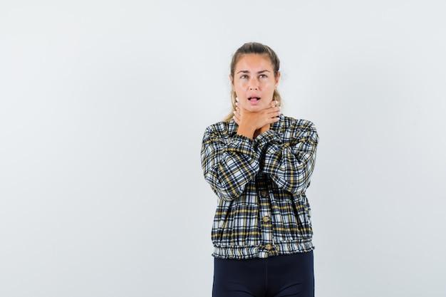 シャツ、ショートパンツの喉の痛みに苦しんでいる若い女性と病気に見えます。正面図。