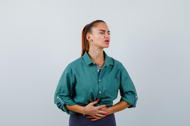 Young lady suffering from stomachache in green shirt and looking painful. front view.
