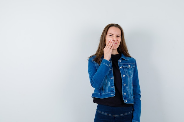 Young lady suffering from toothache in blouse and looking uncomfortable, front view.