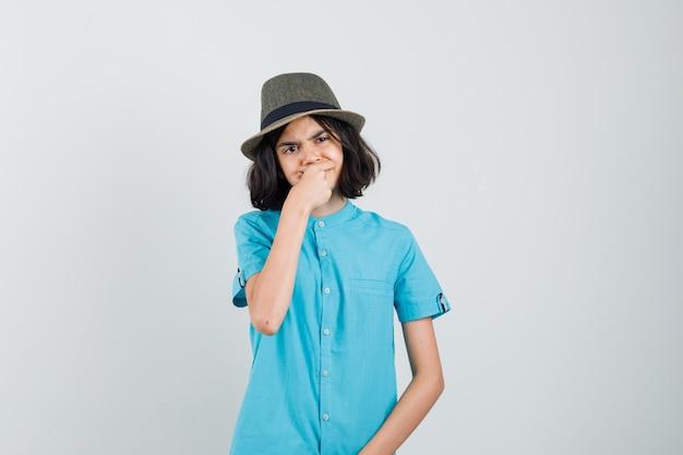 Giovane donna che soffre di mal di denti in camicia blu, cappello e sguardo turbato.