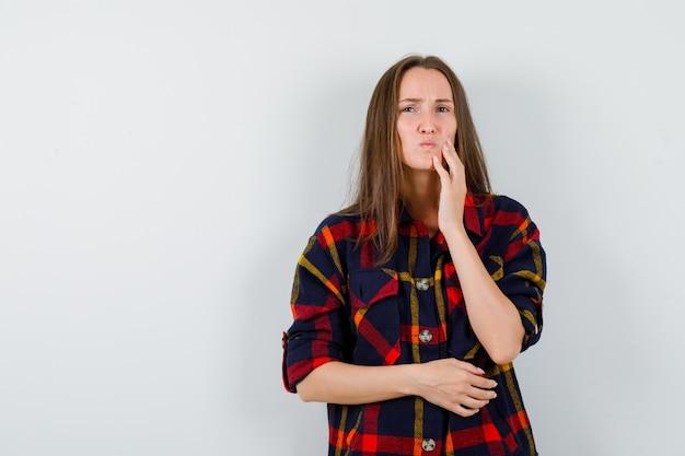 カジュアルなシャツで歯痛に苦しんでいる若い女性と不快に見える、正面図。
