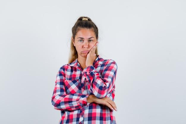 チェックシャツの歯痛に苦しんでいて、動揺している若い女性。正面図。