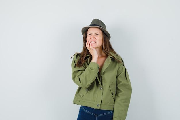 ジャケットのズボンの帽子の歯痛に苦しんでいて、不快に見える若い女性