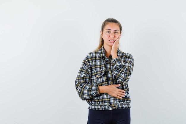 シャツ、ショートパンツの歯痛に苦しんでいて、不快に見える若い女性。正面図。