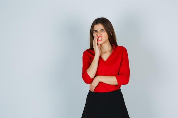 Giovane donna che soffre di mal di denti in camicetta rossa, gonna e aspetto indisposto