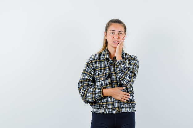 Young lady suffering from toothache in shirt, shorts and looking uncomfortable , front view. Free Photo